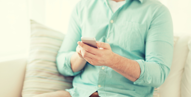 close up of man sitting with smartphone at home