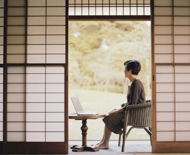 Senior woman sitting beside open doorway, using laptop, side view