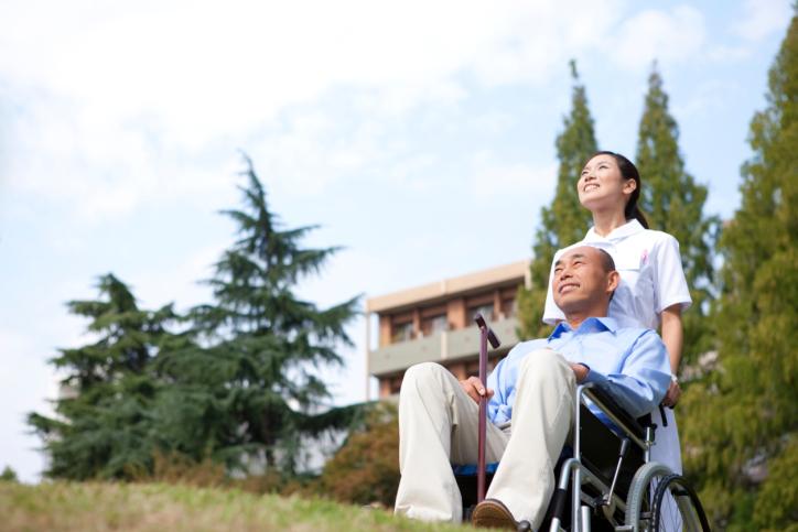 Nurse pushing man on wheelchair